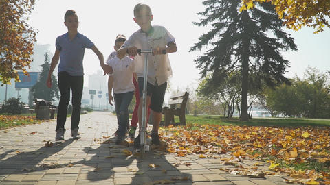 The boy rides a scooter in the autumn park. Friends are catching up with a boy Live Action