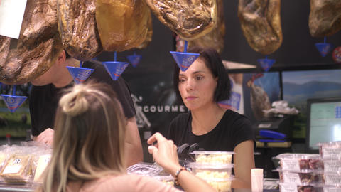 VALENCIA, SPAIN - SEPTEMBER 22, 2018. Beautiful woman sells jamon, cheese and ビデオ