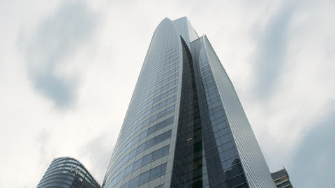 Bottom view of the tall building made of steel and glass, modern architecture ビデオ