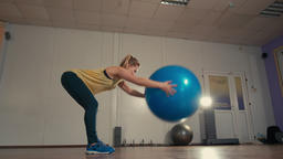 Young Sporty Lady is Exercising alone with Fitball at Hands in Training Gym ビデオ
