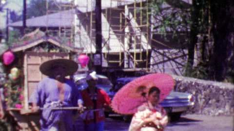 1964: Japanese style parade man pulling traditional merchant cart Footage