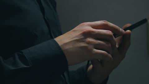 Man uses a smartphone in a dark room ビデオ