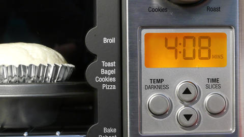 Motion of cup cake baking and time counting down inside toaster oven at kitchen Live Action