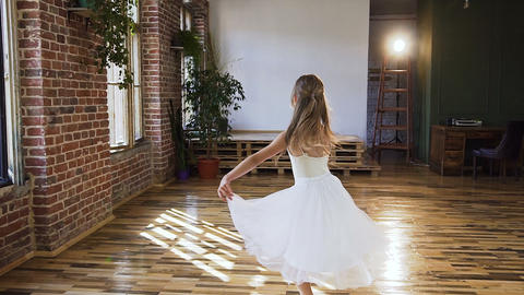 Graceful teen girl in white dress tutu practicing ballet in the modern ballet Live Action