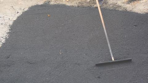 Road street repairing works. Worker during asphalting road ビデオ