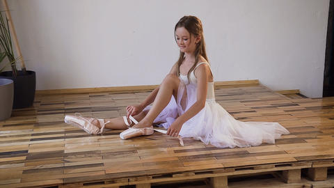 Ballerina change their shoes into special ballet shoes, white pointe shoes, lace Live Action