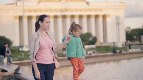 Young mom walking with playful daughter on edge of summer fountain in summer Live Action