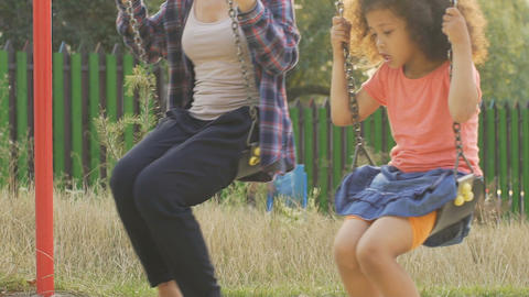 Carefree big and little sisters swinging in backyard, happy summer holidays Footage