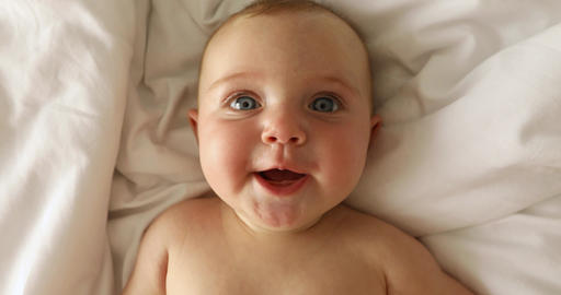 Newborn baby girl laughs lying on her back Live Action