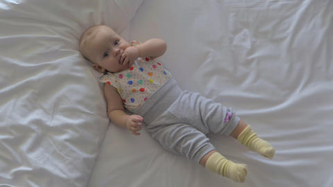 Quiet baby girl on the bed at home Footage
