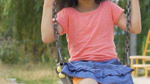 Little African-American girl swinging on playground in summer, slow-motion Live Action