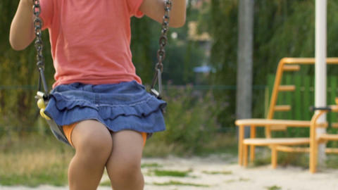 Little biracial girl swinging alone on orphanage playground, dreams about family Footage