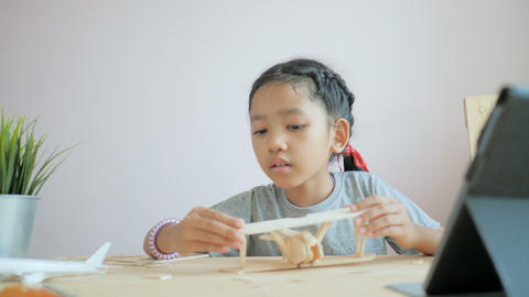 Asian little girl making air plane wooden model, Select focus shallow depth of ビデオ