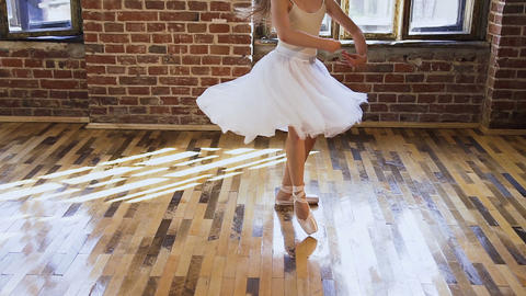 Graceful teen girl in white dress tutu practicing classic elements of ballet in Live Action