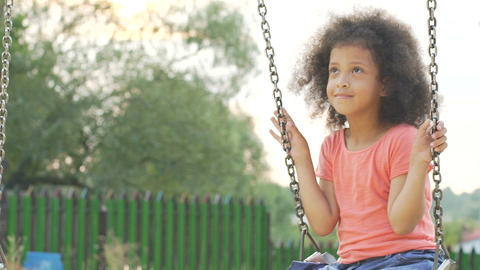 Little curly-haired girl swinging in back yard and dreaming about happy future Footage