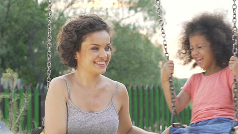 Nanny admiring sincere laughter and genuine joy of little girl on swing, slow-mo Live Action