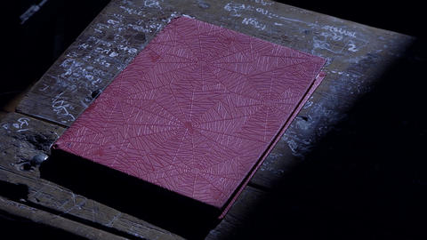 Red Notebook On Old Wooden Table. Dust Particles in the Air Footage