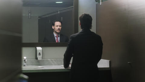 Stressed Latino Businessman Looking At Hairline In Office Toilets Live Action