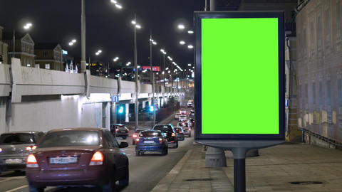 Billboard with a green screen, located on a busy street. Cars move in the Archivo