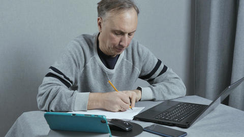 A man writes a work plan. He works at home remotely. Using modern technology Footage