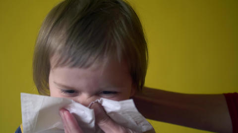 Adult helping little girl to blow nose, face closeup shot Footage