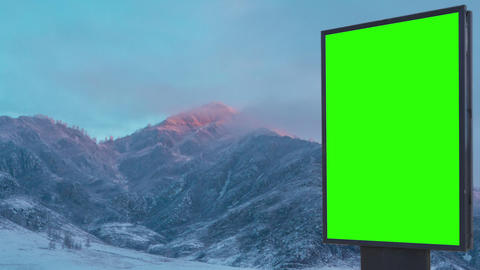 Billboard green screen on the background of sunrise in the snowy mountains Footage