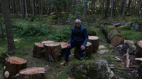 Old man sits sadly among the felled trees Live Action