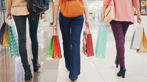 Low shot of female shoppers walking in shopping center together holding gift Footage