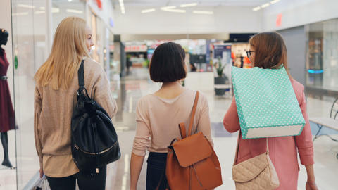 Happy young women friends are walking together in shopping mall holding bright Footage