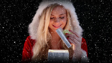 Video composition with falling snow over girl in santas suit holding gift Animation