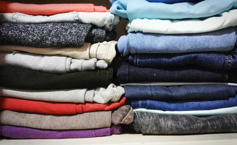 Pants of different colors stacked in a closet フォト