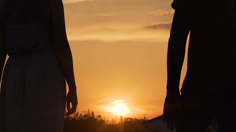 Man and woman standing apart and looking at sunset on horizon, relationship Live Action