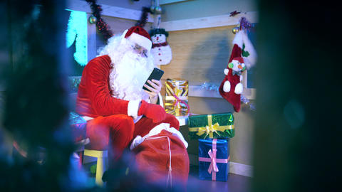 Santa Claus reading messages on the smartphone Live Action