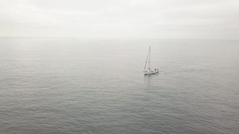 Lonely sailboat lowered sails sailing in sea and overcast sky on background Live Action