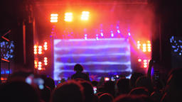 A slow motion of a crowd in front of the bright stage at an open air concert Footage