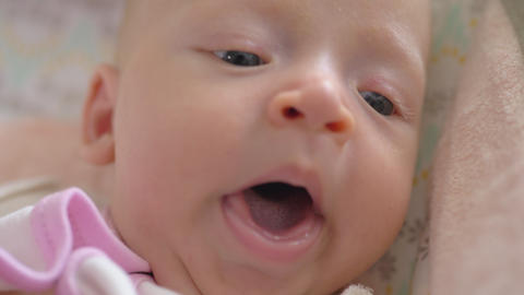 A closeup of a yawning baby girl face Live Action