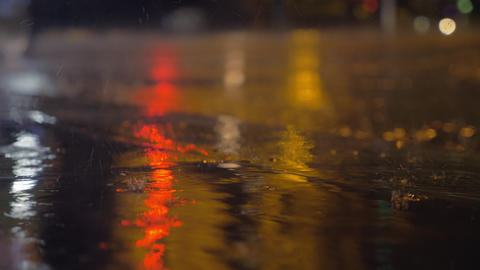 Drizzle and puddles on the asphalt with lights reflection ビデオ