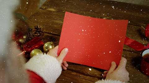 Video composition with falling snow over desk with santa holding red card Animation