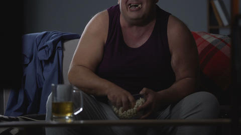 Funny fat guy laughing alone, drinking beer and eating, unhealthy lifestyle Live Action