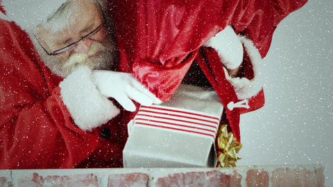 Video composition with falling snow over santa trowing gifts in to chimney Animation