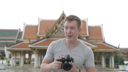 Young happy tourist man photographing against view of the Buddhist temple in ビデオ
