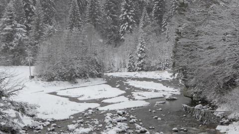 Handheld shot of mountain river during snowfall GIF