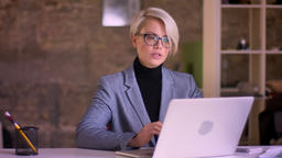 Portrait of short-haired businesswoman in glasses working with laptop in office Footage