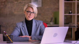 Portrait of blonde short-haired businesswoman in glasses and hands crossed on Archivo