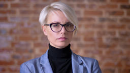 Portrait of middle-aged blonde short-haired woman in glasses watching seriously Footage