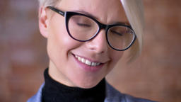 Close-up portrait of blonde short-haired woman in glasses smiling gladly into Footage