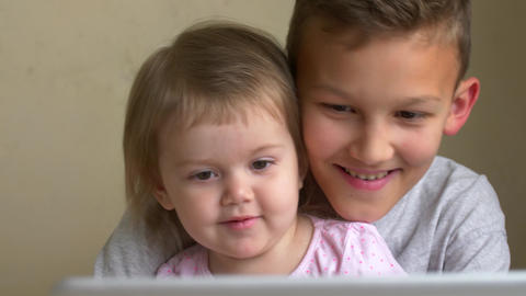 Children watch laptop video, smile, laugh and have fun Footage