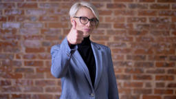 Portrait of caucasian blonde short-haired woman in glasses gesturing finger-up Footage