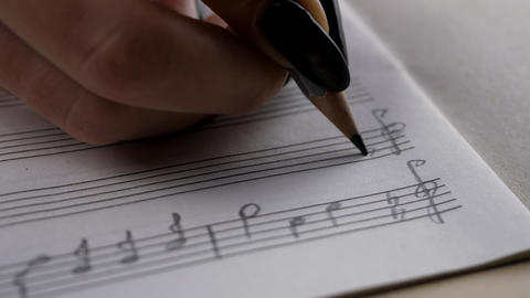Musician or composer hand writes a song or a musical work GIF