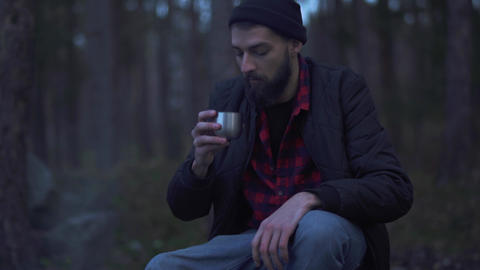 Young bearded man sit in the forest near bonfire and put beverage in a cup from Live Action
